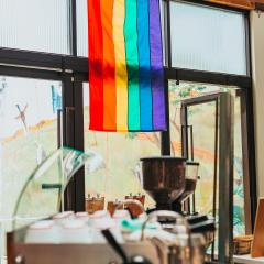 A rainbow flag hanging against a window